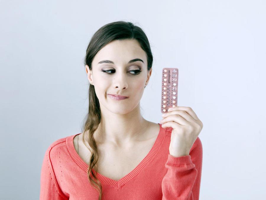 Mujer con cara de decepción mirando píldoras anticonceptivas