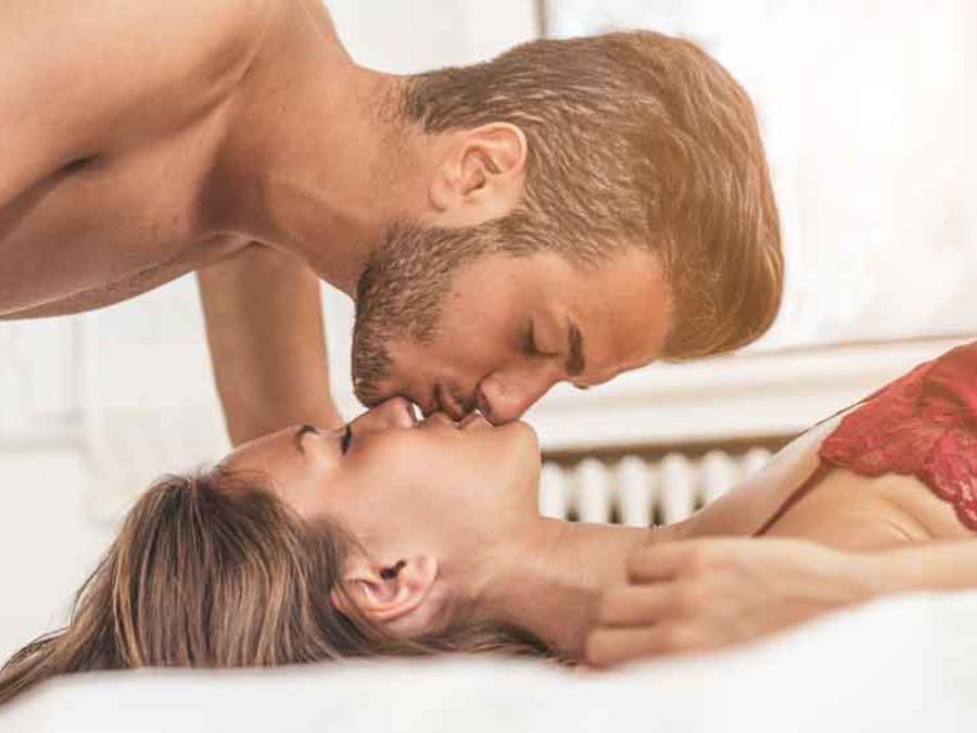 Pareja besándose acostados en la cama