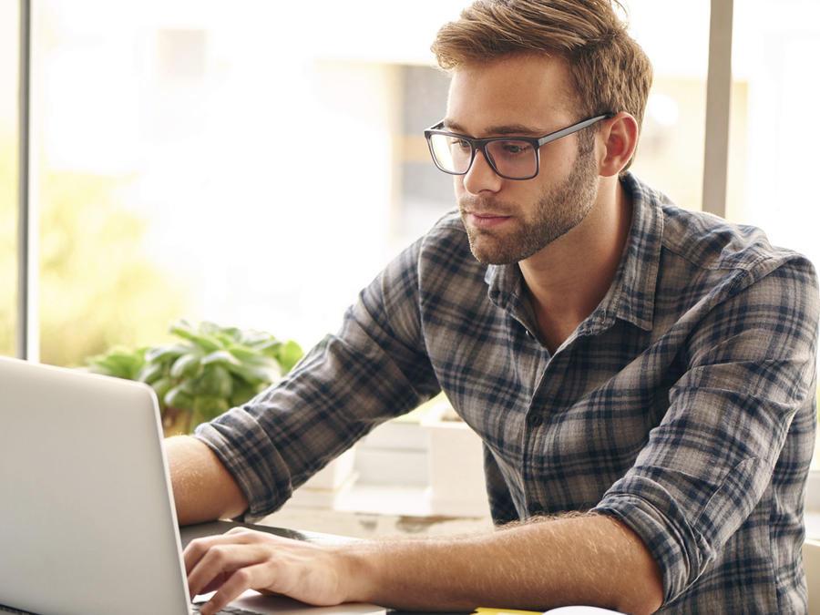 Hombre joven con gafas usando una laptop