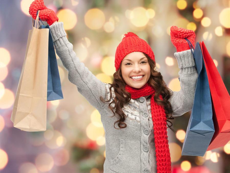 Mujer en ropa de invierno sonriendo con sus compras navideñas