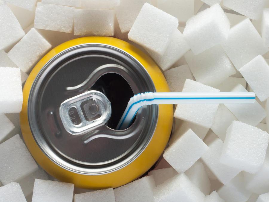 Lata de soda enterrada entre cubos de azúcar
