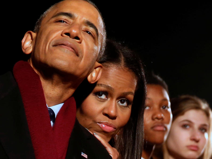 Obama and the first lady cuddle together as they participate in the National Christmas Tree lighting in Washington