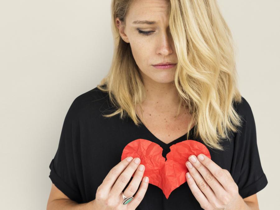 Mujer triste sosteniendo un corazón roto