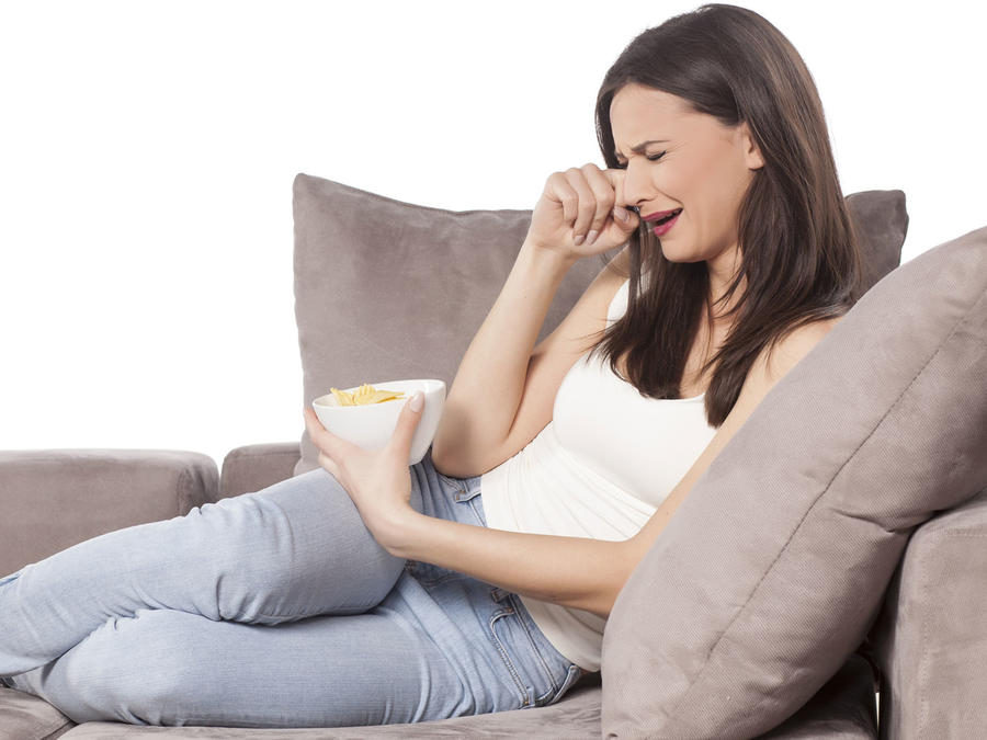 Mujer en el sofa llorando con un bol de Nachos