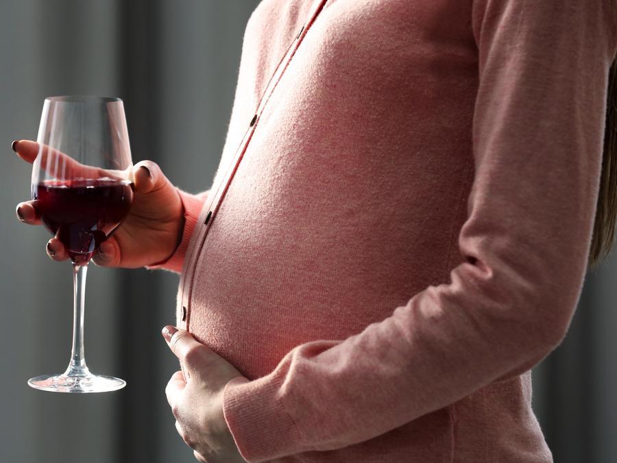 Mujer embarazada sosteniendo copa de vino