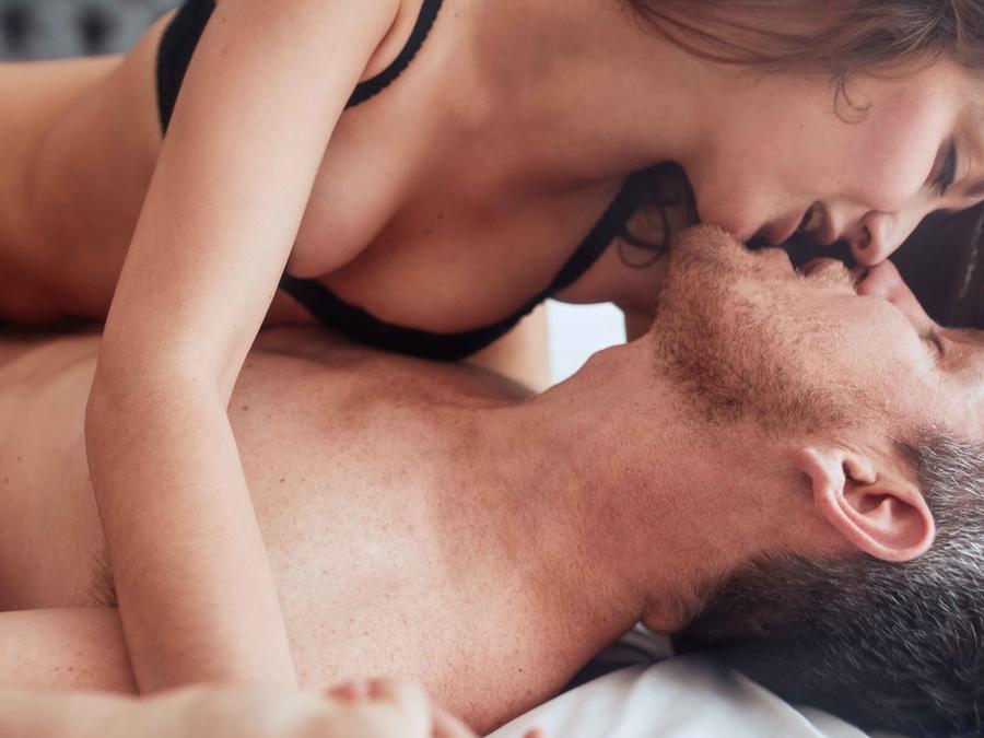 Pareja besándose en la cama en ropa interior