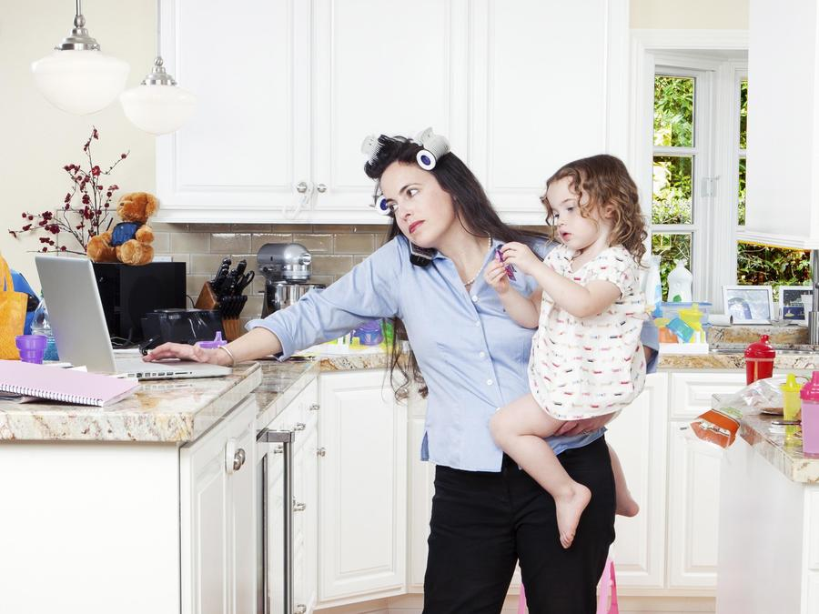 Frustrated mother using laptop and caring for children