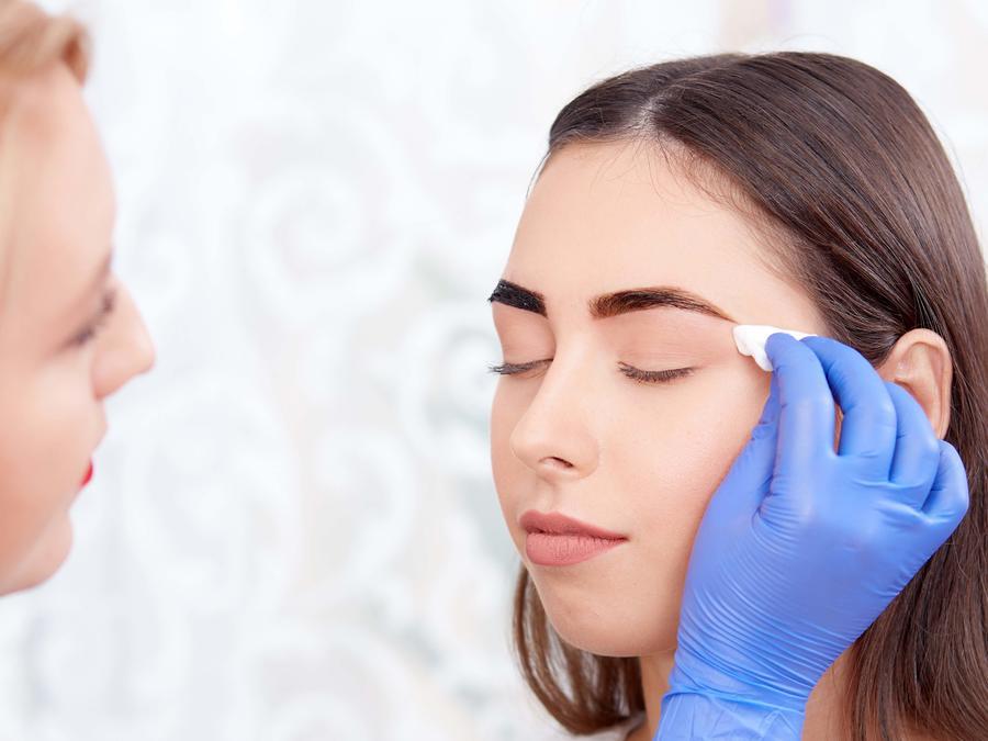 Esteticista aplicando tinte en las cejas a una mujer