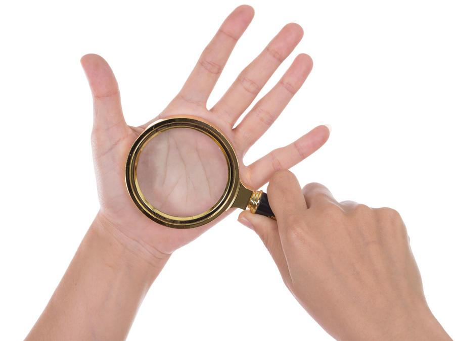 Hombre con lupa sobre la palma de su mano