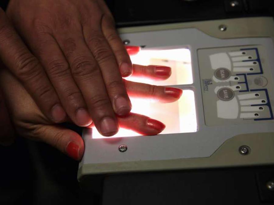 Agente toma huellas dactilares de una mujer