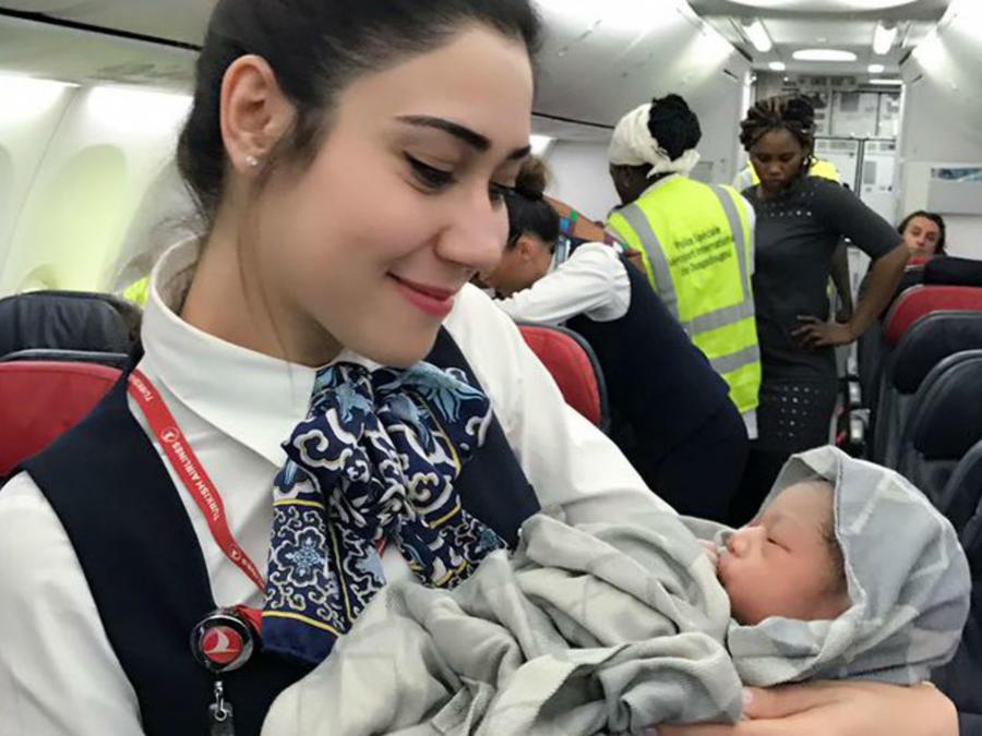 Azafata de Turkish Airlines cargando a una bebé