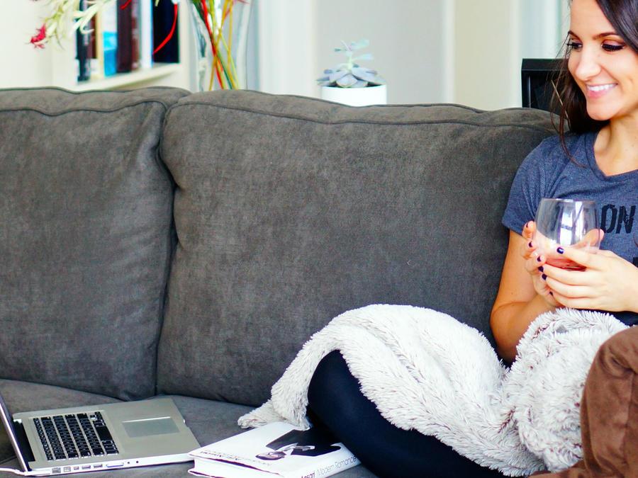 Mujer sentada en el sofá viendo la computadora