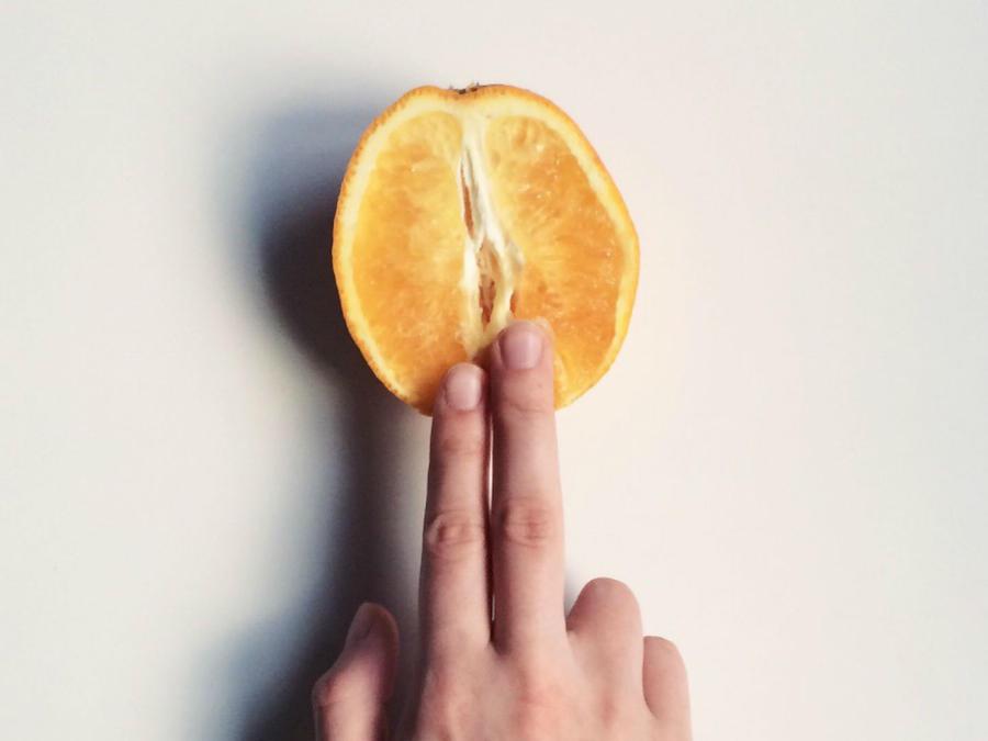 Dedos tocando una naranja de forma sugerente