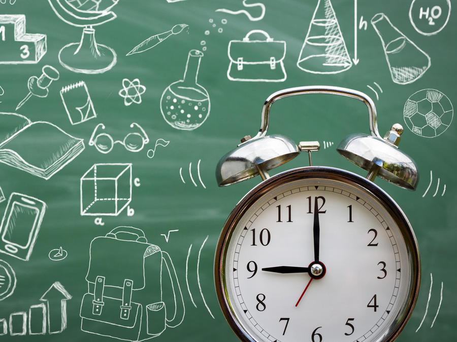 Reloj despertador frente a una pizarra escolar