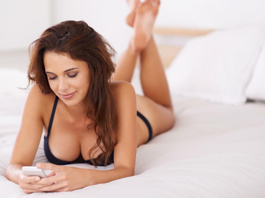 Mujer en lencería mirando el celular en la cama