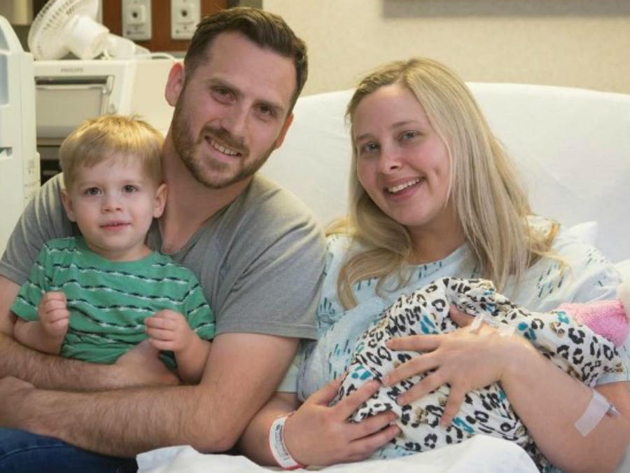 Keri Young y su familia sosteniendo a su bebé en el hospital