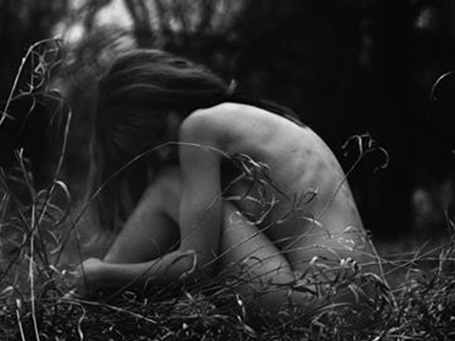 Mujer desnuda sentada en el pasto