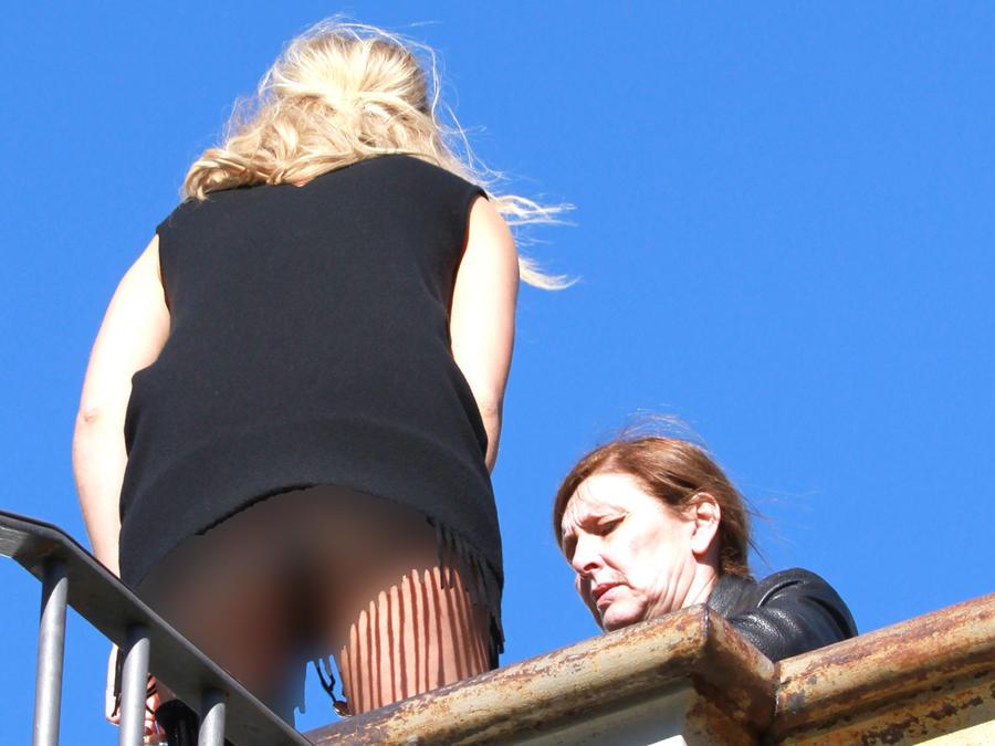 Suki Waterhouse agachada mostrando el trasero