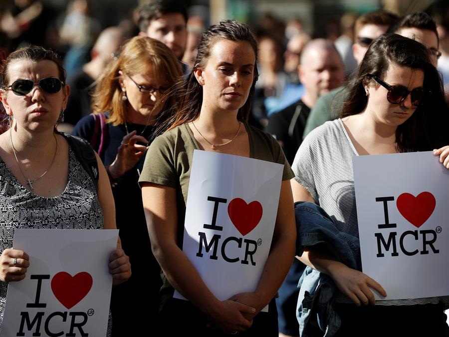 Women wait to take part in a vigil for the victims of an attack on concert goers at Manchester Arena, in central Manchester