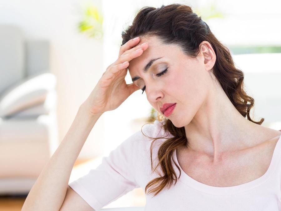 Mujer en sus treintas con dolor de cabeza