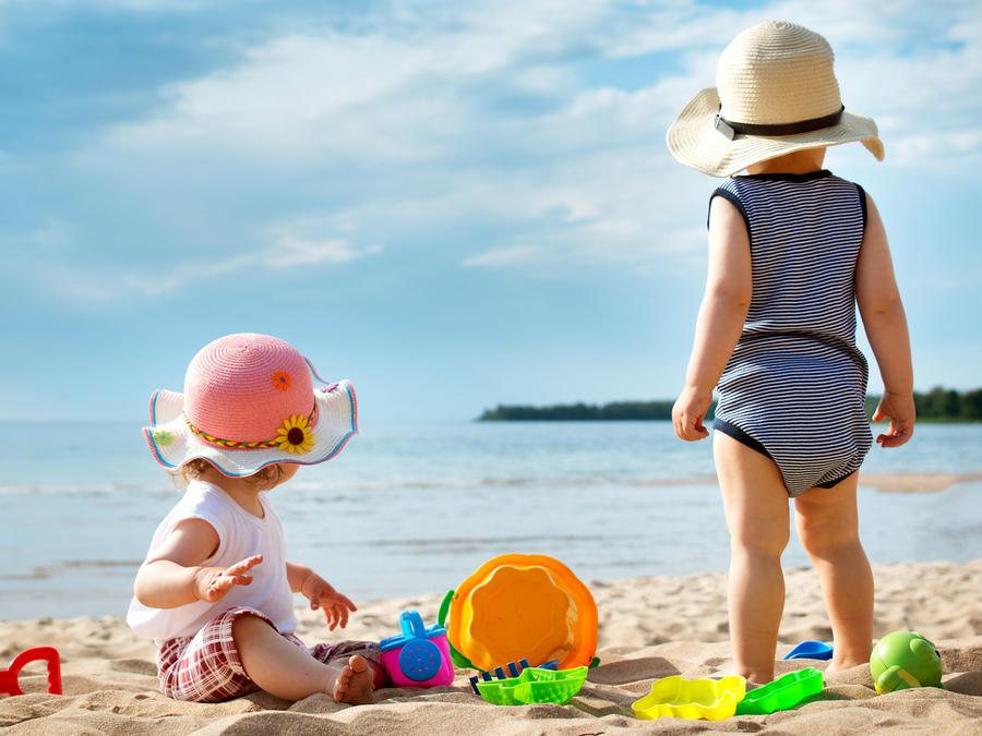 Niños pequeños jugando en la arena frente al mar