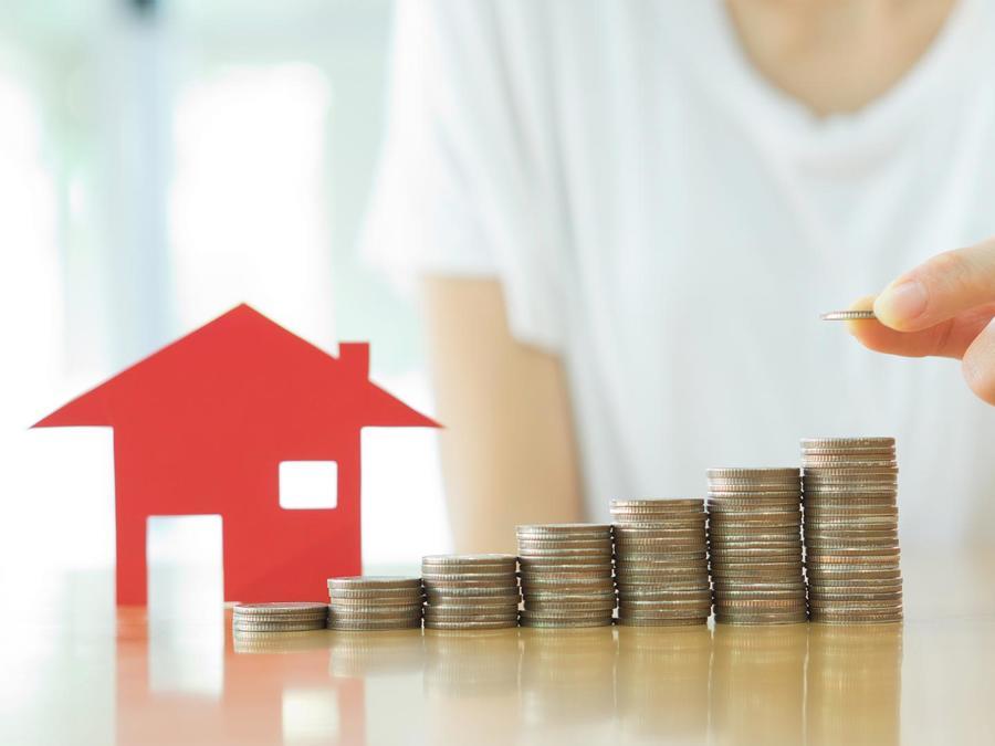 Persona haciendo pilas de monedas con una casa de papel