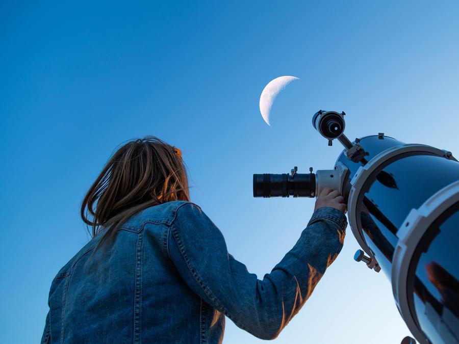 Mujer mira la luna con telescopio