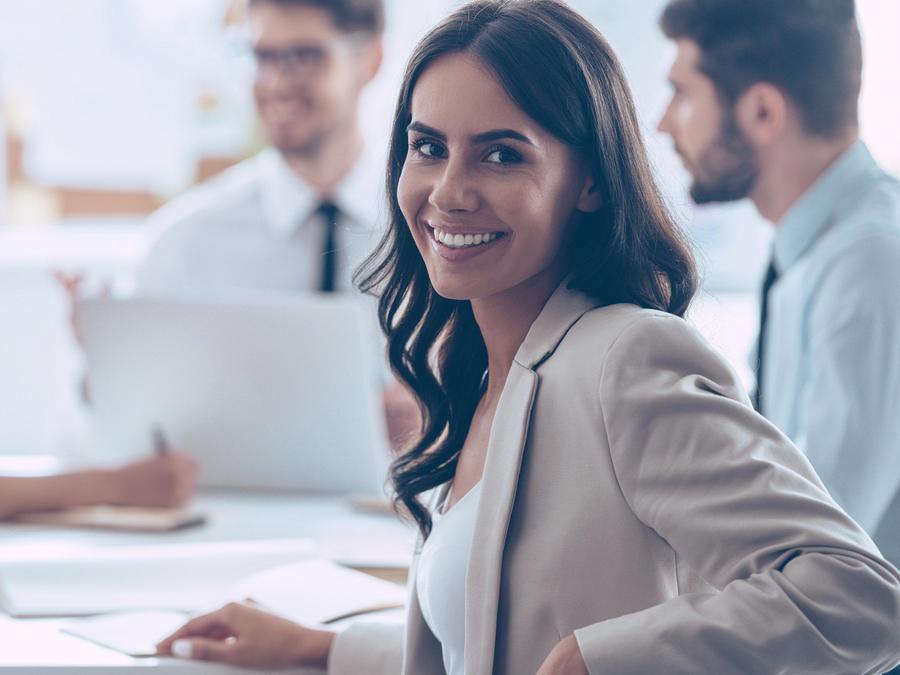 Mujer sonriendo al trabajar en grupo