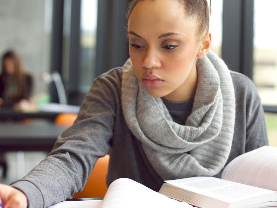 Adolescente estudiando en biblioteca