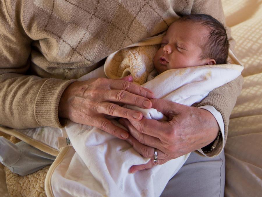 Mujer mayor cargando a un bebé