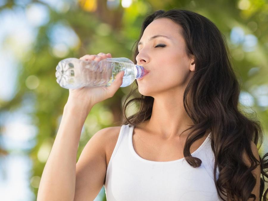 Mujer bebiendo agua embotellada