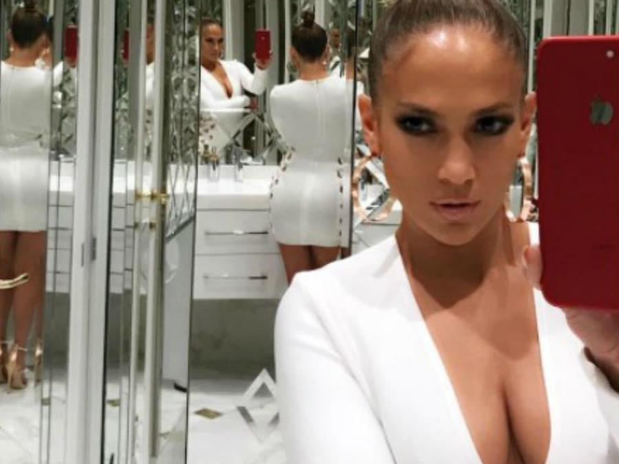 Jennifer Lopez tomándose una selfie en un baño blanco
