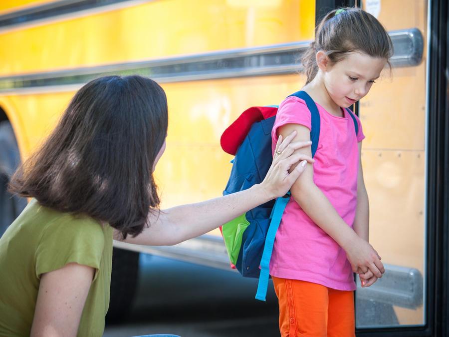 Niña despidiéndose frente al autobús escolar