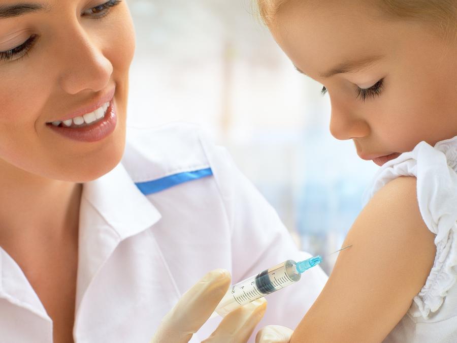 Médica dando una vacuna a niña