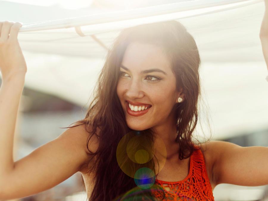 Mujer sonríe bajo el sol