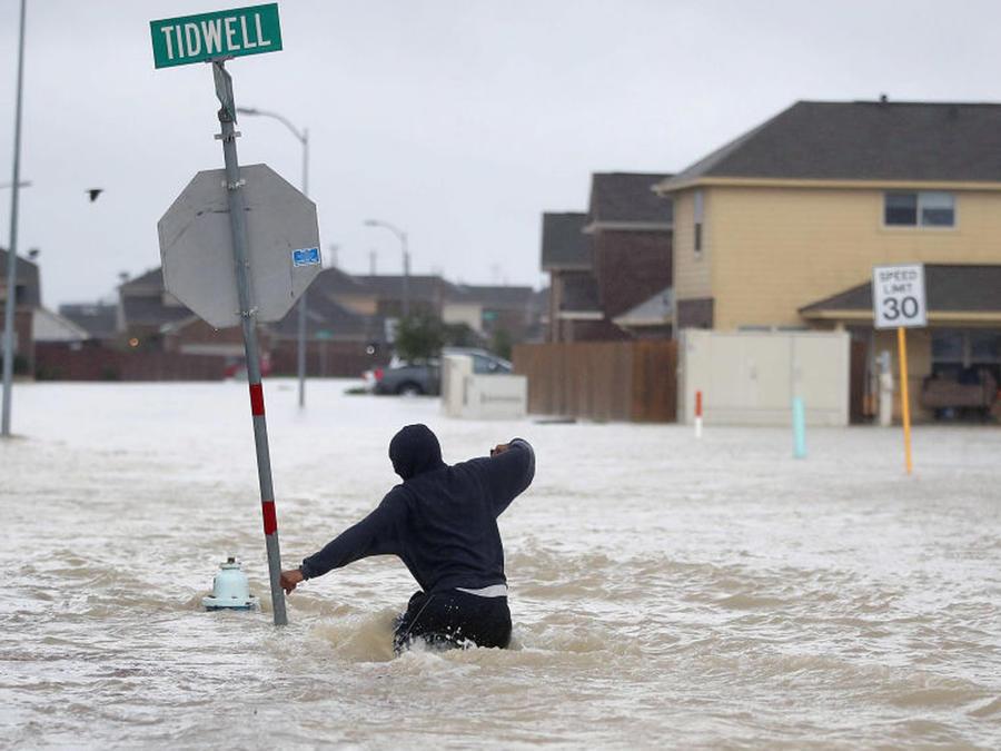 Hombre caminando en medio de la inundación causada por el huracán Harvey de 2017, Houston, Texas