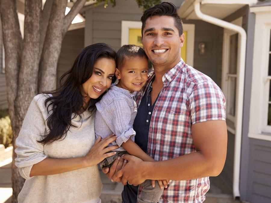 Familia de origen latino frente a su casa