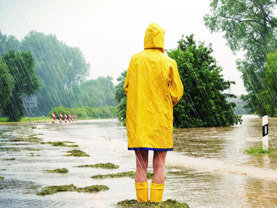Niño con impermeable bajo la lluvia