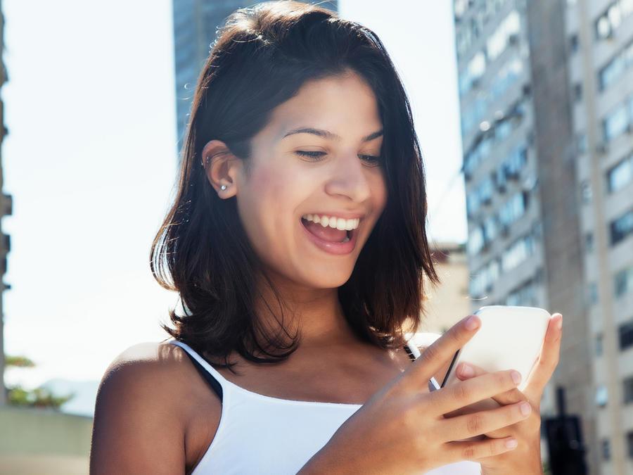 Mujer sonríe con smartphone