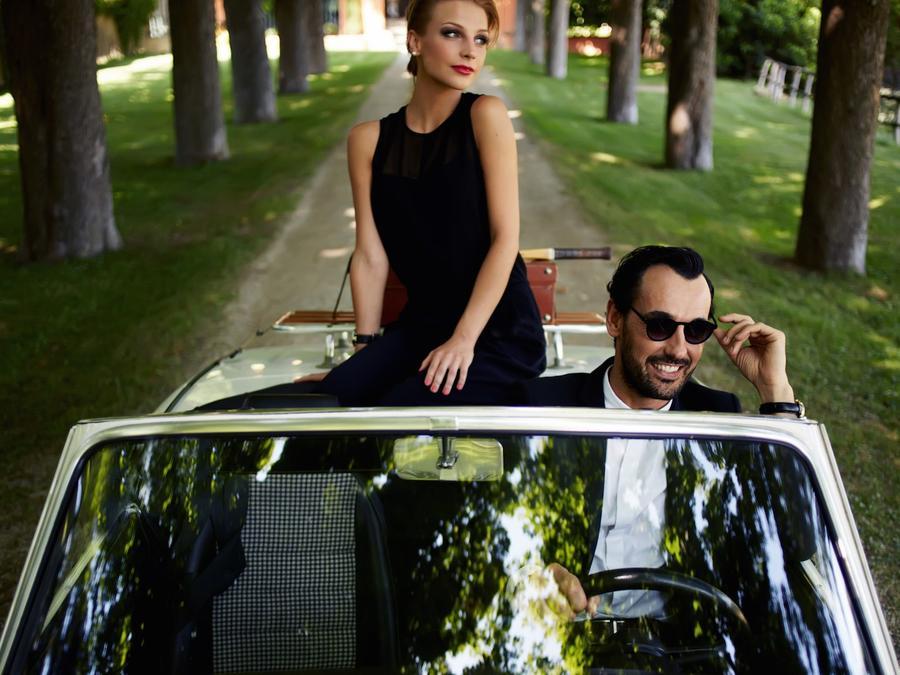 Mujer y hombre en carro de lujo