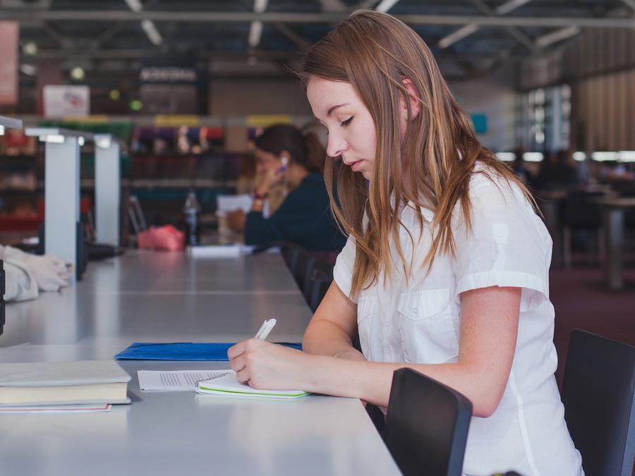 Chica joven estudiando en la biblioteca