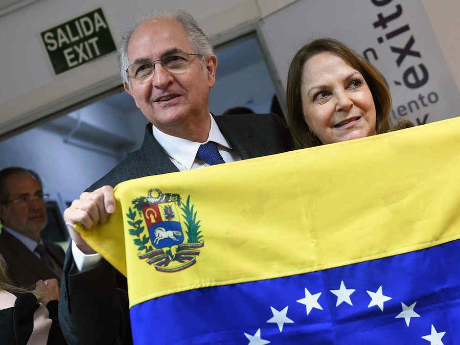 El alcalde metropolitano de Caracas y opositor venezolano, Antonio Ledezma (i), posa junto a su mujer Mitzy Capriles (d), tras una bandera de Venezuela, en Madrid.