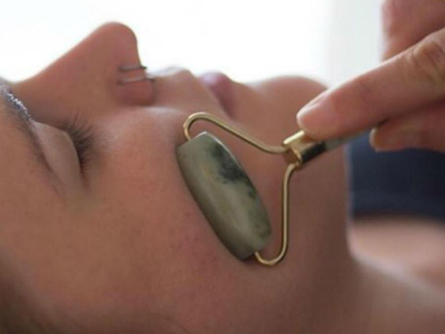 Mujer frotando su cara con un rodillo de jade