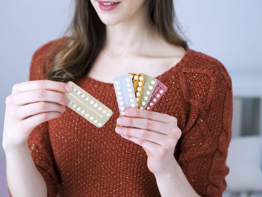 Mujer mostrando sus píldoras anticonceptivas