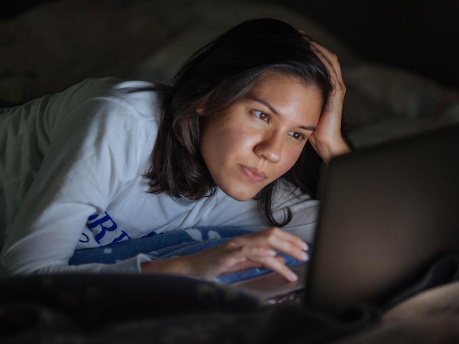 Mujer viendo la pantalla de su computadora en la cama