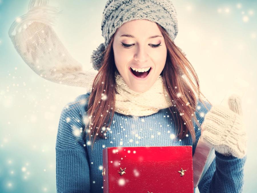 Mujer abrigada abriendo regalo