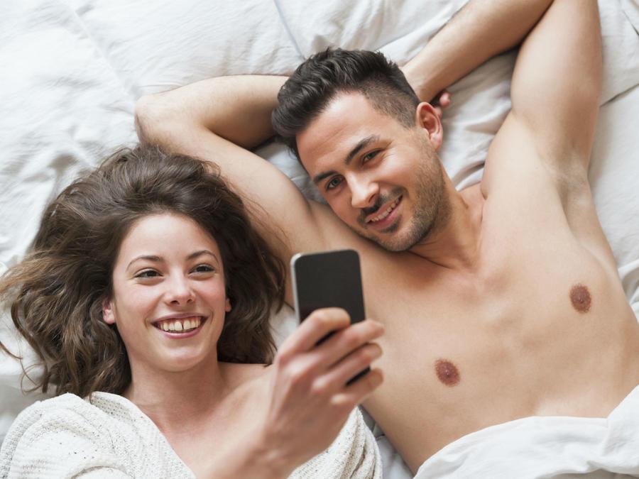 Pareja en la cama con el celular
