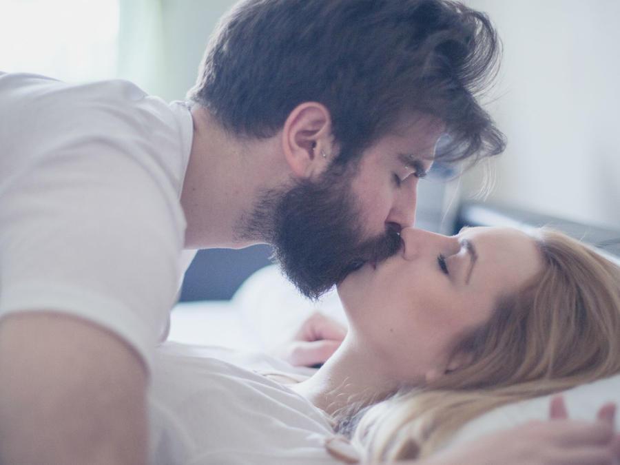 Pareja acostados en la cama besándose