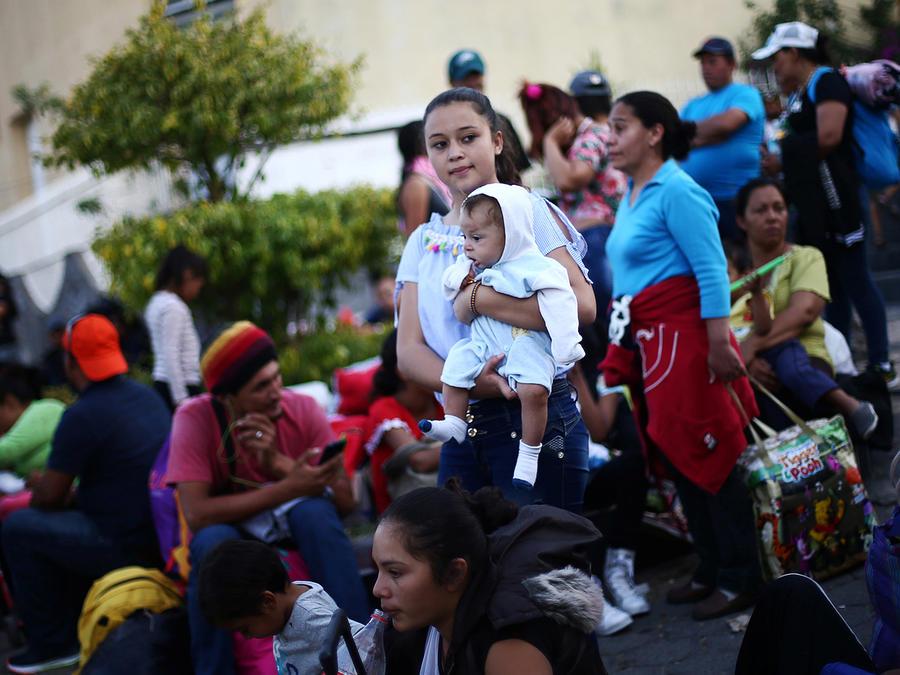 Una mujer que viaja en la caravana de migrantes sostiene un bebé en brazos mientras espera el  autobús a Mazatlán, México el 19 de abril de 2018