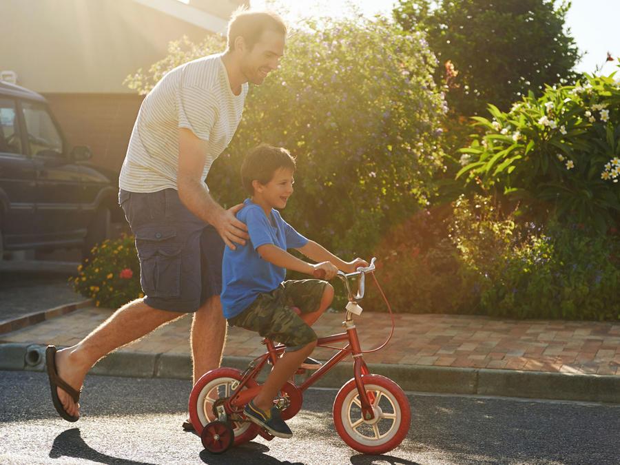 Padre e hijo aprendiendo a andar en bici